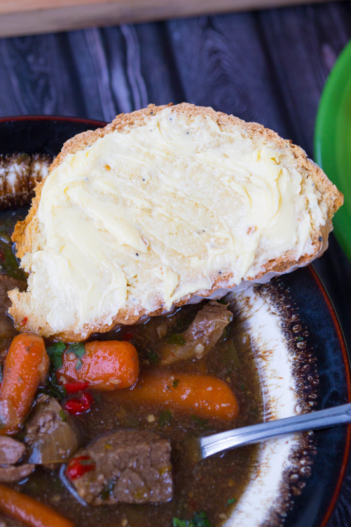 Everything Irish Soda Bread Slice with Butter on the side of Beef Stew