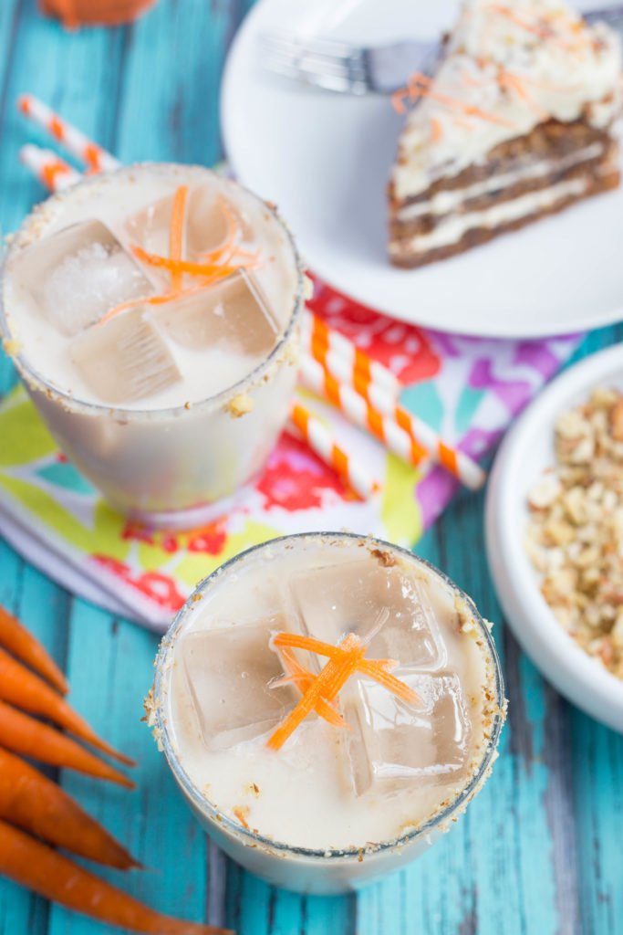 Overhead shot of carrot cake white Russians with carrots, orange and white straws, pecans, and cake