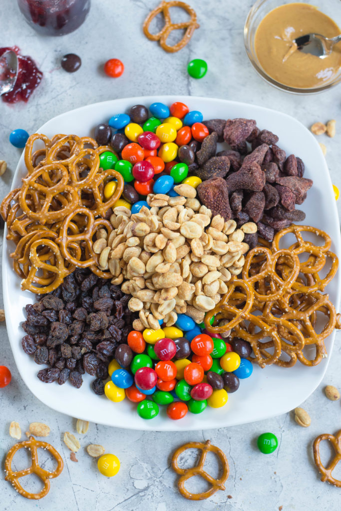 Peanut Butter and Jelly Trail Mix Ingredients: Peanut butter m&ms, dried strawberries, pretzels, raisins, roasted peanuts on a white plate