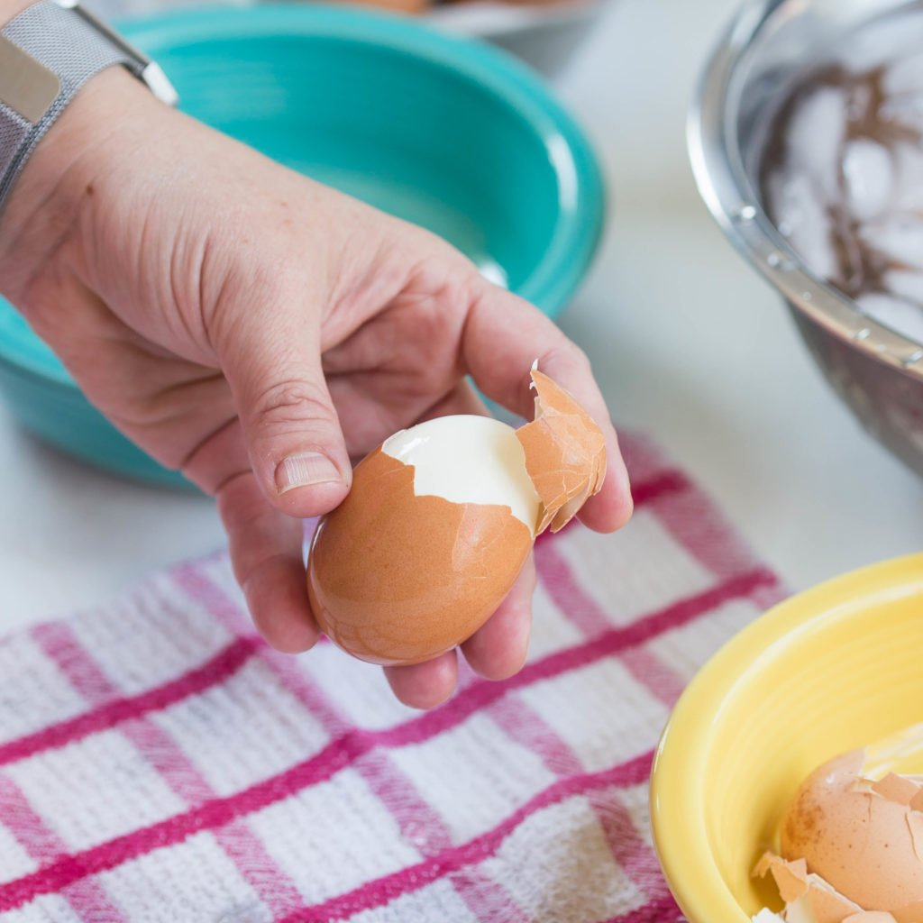 Hand holding an easy peel hard boiled egg with shell halfway off the top